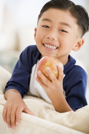 snacking: Young boy eating apple in living room smiling
