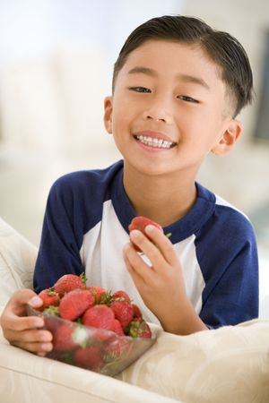 offset view: Young boy eating strawberries in living room smiling