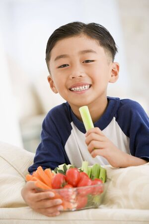 snacking: Young boy eating bowl of vegetables in living room smiling