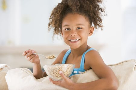 Young girl eating cereal in living room smiling photo