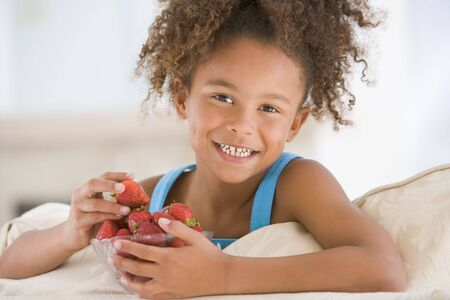 eating in: Young girl eating strawberries in living room smiling