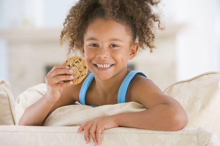 meisje eten: Jonge meisje eten van de cookie in de woonkamer die lacht Stockfoto