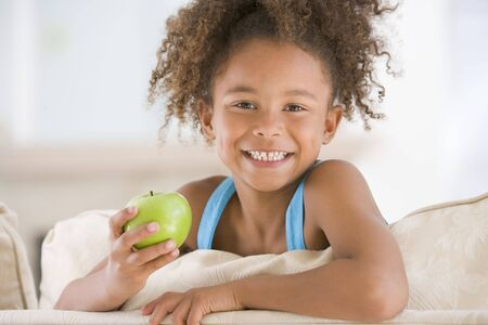 childrens food: Young girl eating apple in living room smiling