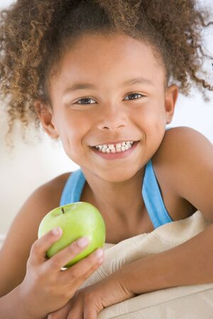 snacking: Young girl eating apple in living room smiling