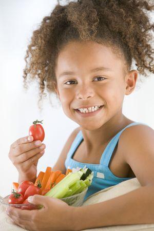 root vegetables: Giovane ragazza mangiare ciotola di verdure in salotto sorridendo