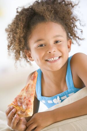eating out: Young girl eating pizza slice in living room smiling