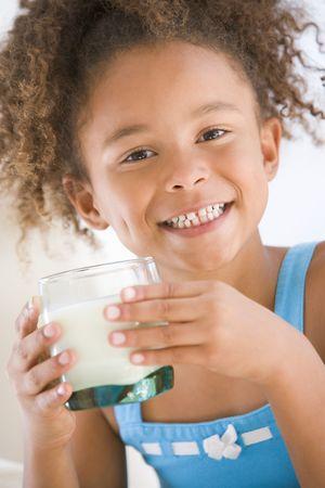 tomando leche: Ni�a de la leche de adentro sonriendo  Foto de archivo