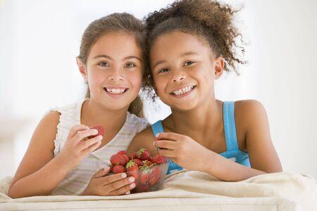 ni�os comiendo: Dos ni�as de comer fresas en el sal�n sonriendo Foto de archivo