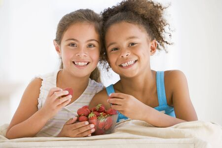 Two young girls eating strawberries in living room smiling photo