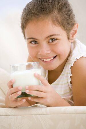 latte fresco: Giovane ragazza bevendo il latte nel soggiorno sorridente  Archivio Fotografico