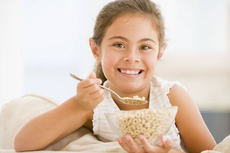 Young girl eating cereal in living room smiling Stock Photo - 3506639