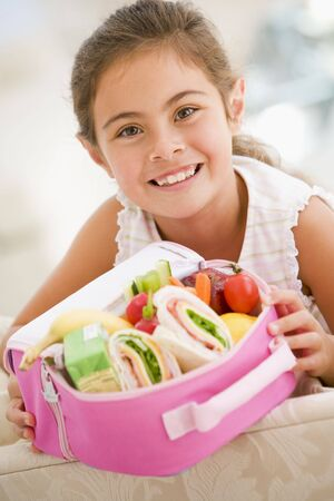 Young girl holding packed lunch in living room smiling photo