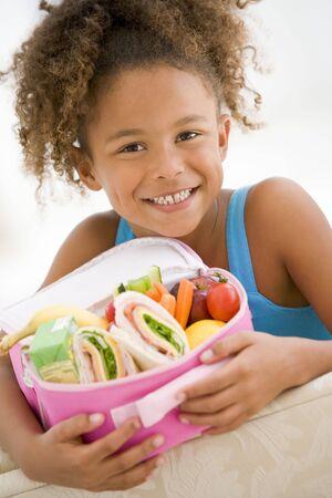 lunchen: Jong meisje bedrijf lunchpakket in de woonkamer glimlachende Stockfoto