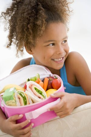 Young girl holding packed lunch in living room smiling Stock Photo - 3507145