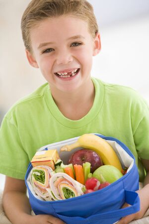 Young boy holding packed lunch in living room smiling photo