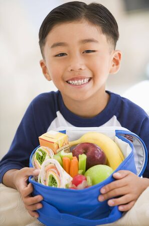 Young boy indoors with packed lunch smiling photo