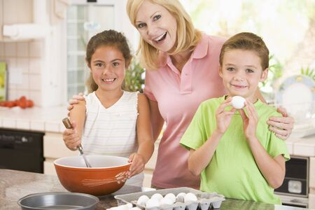 egg whisk: Woman and two children in kitchen baking and smiling
