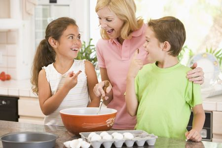 Woman and two children in kitchen baking and smiling photo