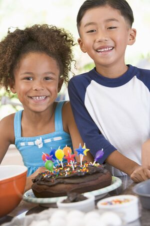 Two children in kitchen with birthday cake smiling