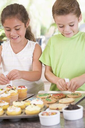 childrens food: Two children in kitchen decorating cookies smiling