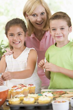 Woman with two children in kitchen decorating cookies smiling photo