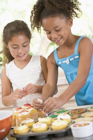 snacking: Two children in kitchen decorating cookies smiling