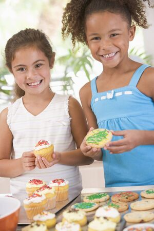 Two children in kitchen decorating cookies smiling photo