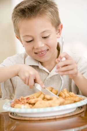 Young boy indoors eating fish and chips smiling photo