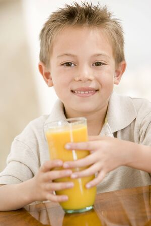 Young boy indoors with orange juice smiling photo