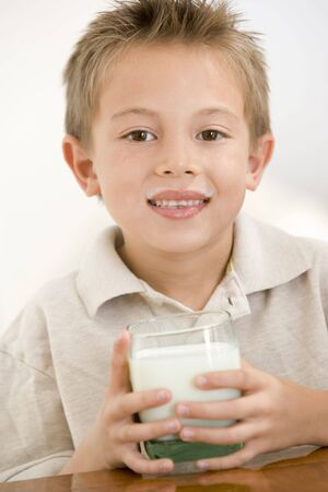 Young boy indoors drinking milk smiling photo