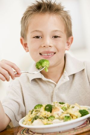 childrens food: Young boy indoors eating pasta with brocolli smiling