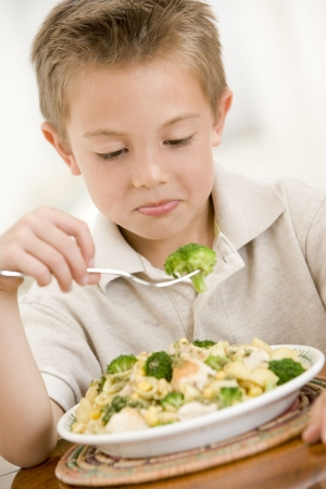 fussy: Young boy indoors eating pasta with brocolli
