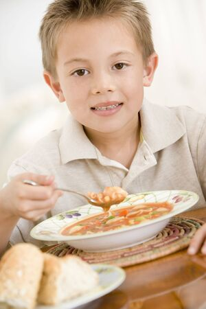 Young boy indoors eating soup photo