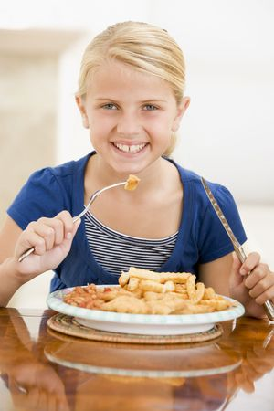 fish fry: Young girl indoors eating fish and chips smiling Stock Photo