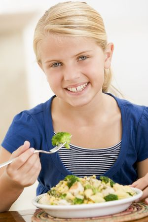 brocolli: Young girl indoors eating pasta with brocolli smiling Stock Photo