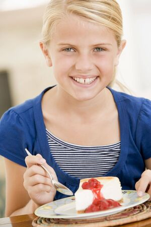 Young girl indoors eating cheesecake smiling photo