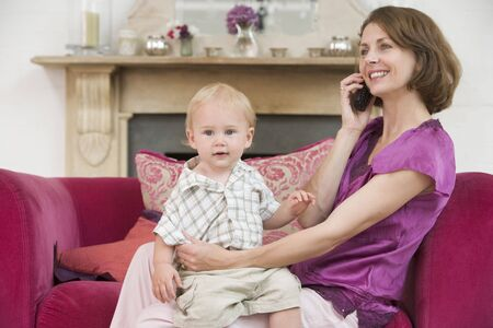 Mother using telephone in living room with  smiling Stock Photo - 3507180