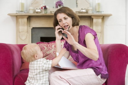 madre trabajadora: Madre utilizando tel�fono en sal�n con fruncir el ce�o