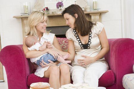 Zwei M�tter im Wohnzimmer mit Baby und Kuchen l�chelnd Stockfoto - 3507160