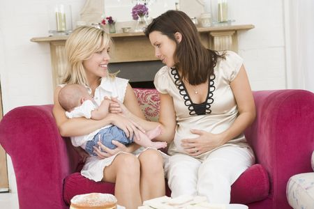 Zwei Mütter im Wohnzimmer mit Baby und Kuchen lächelnd Lizenzfreie Bilder - 3507160