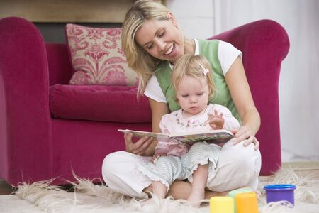twenty four month old: Mother in living room reading book with  smiling Stock Photo