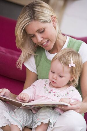 24 month old: Mother in living room reading book with  smiling Stock Photo