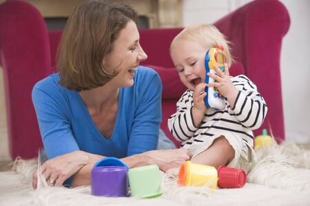 learing: Mother in living room playing with baby smiling Stock Photo