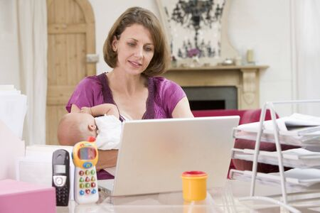 generation x: Mother and baby in home office with laptop Stock Photo