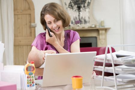 Mother and baby in home office with laptop and telephone photo