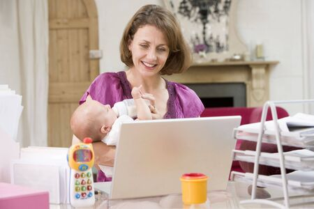 x files: Mother and baby in home office with laptop Stock Photo