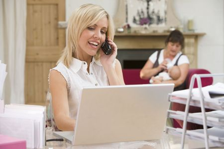 Woman in home office with laptop and telephone with mother and  in background photo