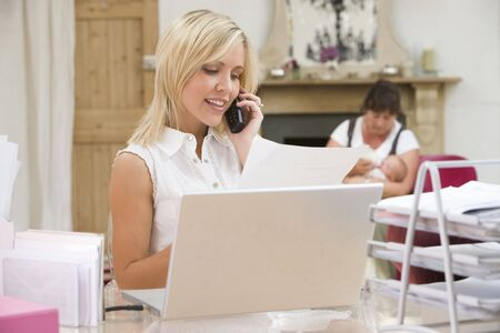 business for the middle: Woman in home office with laptop and telephone with mother and  in background