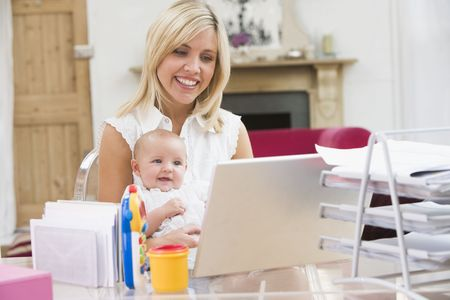 looking for work: Mother and baby in home office with laptop Stock Photo
