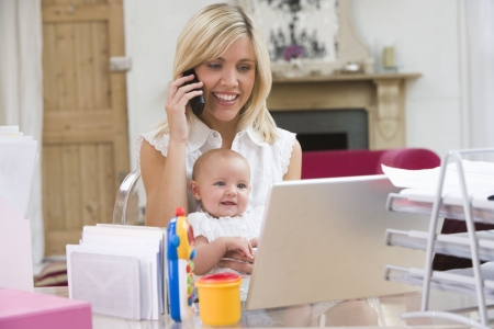 looking for work: Mother and baby in home office with laptop and telephone